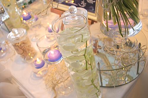 白いテーブルにロウソクやお花が載っている結婚式場の画像