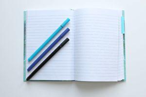 ノートとノートの上に並んだペンの画像