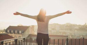 太陽に向かって手を広げる女性の写真
